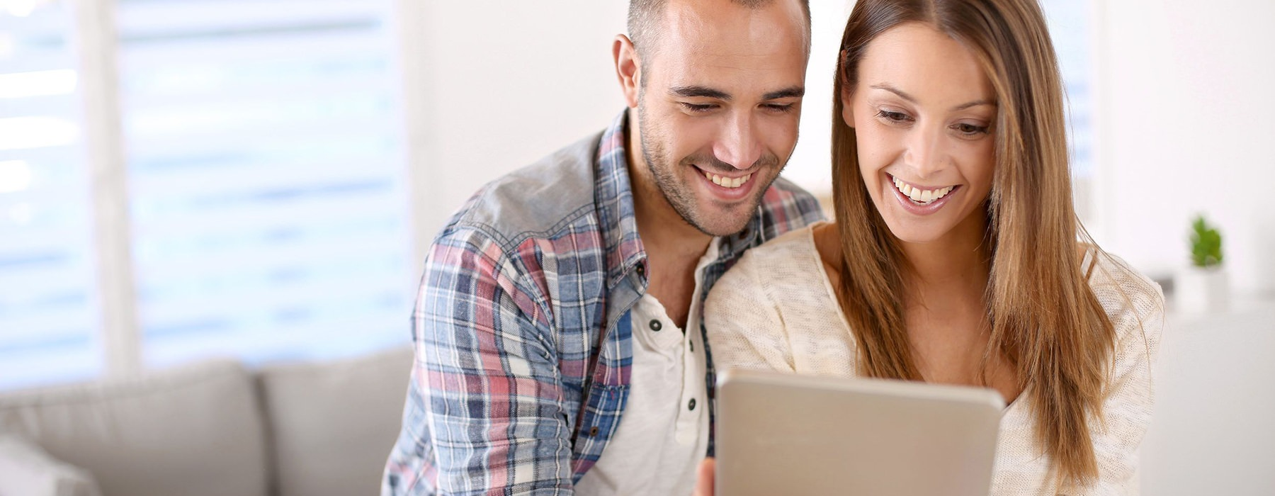 man and woman look at their electronic tablet in their living room